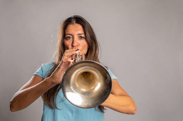 Vrouw trompet spelen op een grijze ruimte