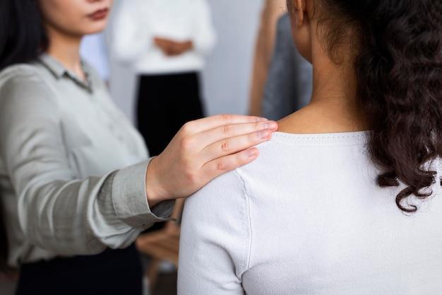 Vrouw troostende persoon tijdens een groepstherapie-sessie