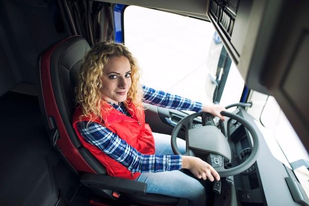Vrouw trucker zit in vrachtwagen voertuig
