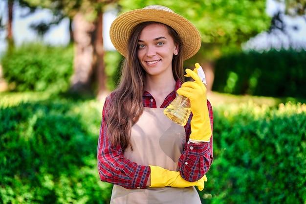 Vrouw tuinman houden spray fles voor het water geven van planten in de tuin
