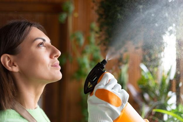Vrouw tuinman thuis in schort en handschoenen met groeiende planten op huis balkon water geven met spray