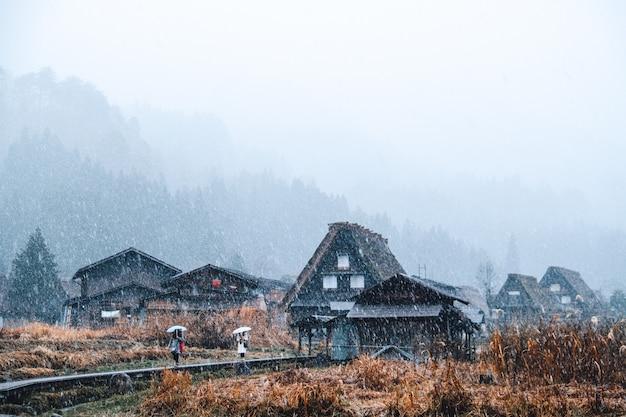 Vrouw twee die op brug loopt wanneer dalende sneeuw in sirakawago, gifu, japan