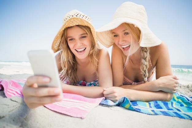 Vrouw twee die op het strand ligt en mobiele telefoon bekijkt