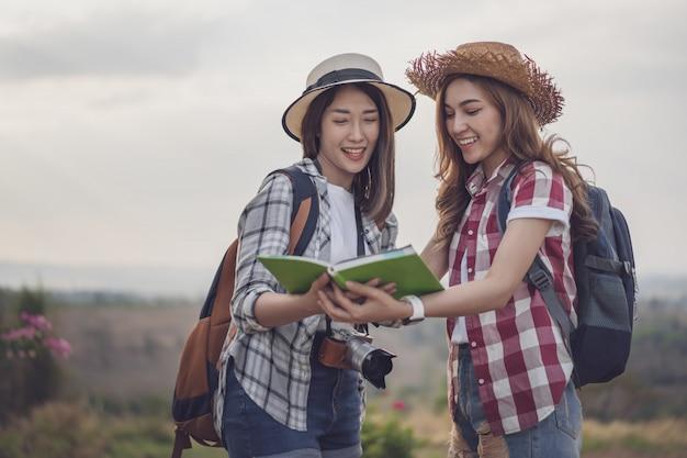 Vrouw twee die richting op plaatskaart zoekt terwijl het reizen