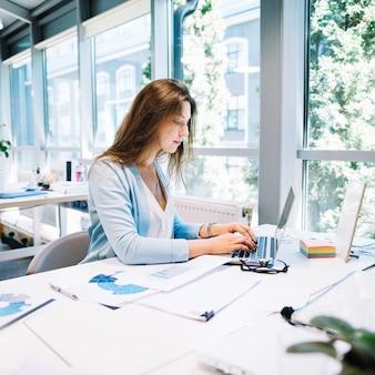 Vrouw typen laptop in kantoor