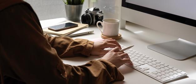 Vrouw typen op computertoetsenbord op wit bureau met smartphone en kantoorbenodigdheden