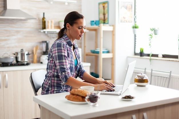 Vrouw typen op laptop genieten van groene thee tijdens het ontbijt in de keuken