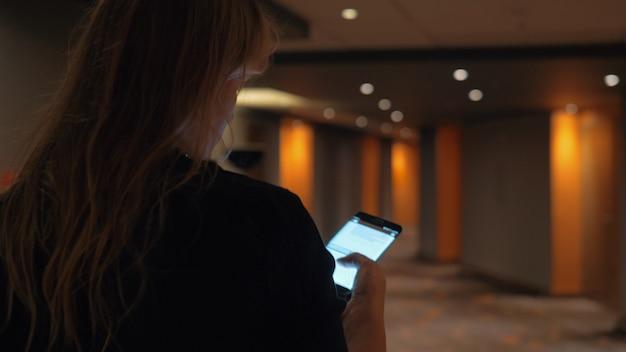 Vrouw typt bericht op weg naar hotelkamer