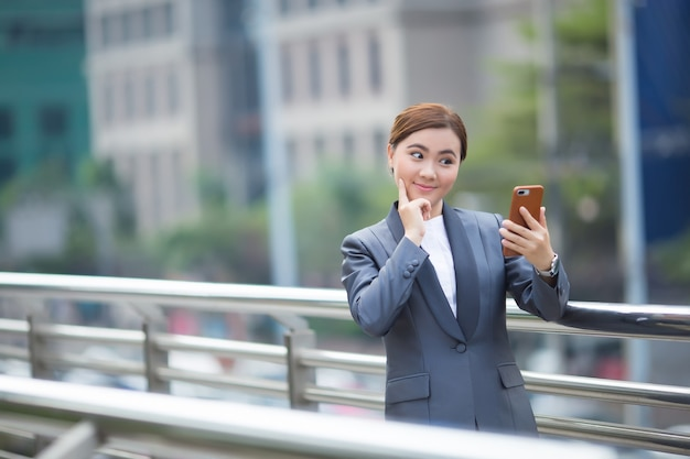 Vrouw typt de smartphone en ze voelt zich gelukkig