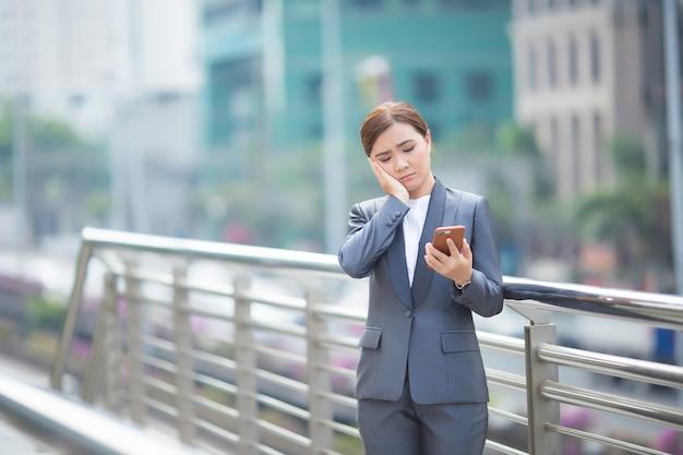 Vrouw typt de smartphone en ze voelt zich verdrietig