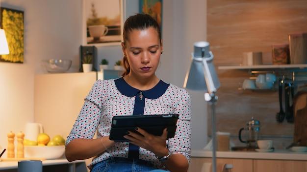 Vrouw typt op tablet die 's avonds laat vanuit huis op een stoel in de keuken zit. drukke gerichte werknemer met behulp van moderne technologie netwerk draadloos overuren schrijven, zoeken.
