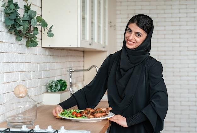 Vrouw uit het midden-oosten die thuis in abaya kookt