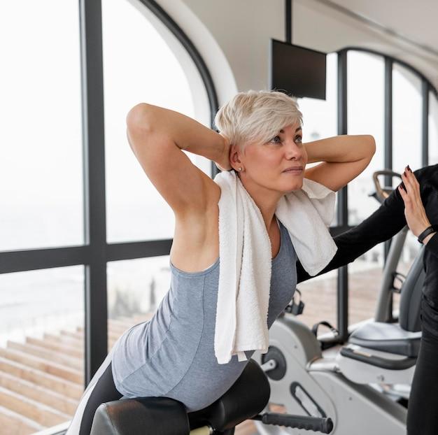 Vrouw uit te werken en wordt geholpen door personal trainer