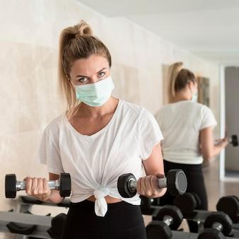 Vrouw uit te werken met gewichten in de sportschool terwijl ze een medisch masker draagt