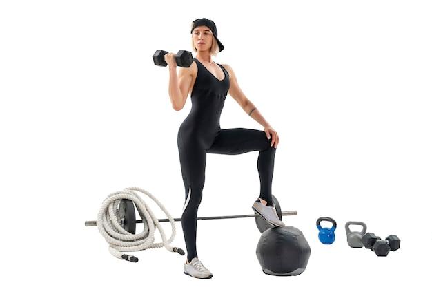Vrouw uit te werken met halters vrouw omringd door sportartikelen