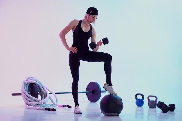 Vrouw uit te werken met halters vrouw omringd door sportuitrusting