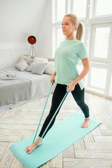 Vrouw uit te werken op mat met elastische band