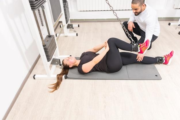 Vrouw uitoefenen op kabel crossover machine met personal trainer op sportschool