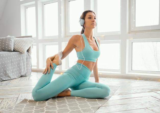 Vrouw uitoefenen op mat en muziek luisteren
