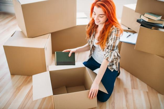 Vrouw uitpakken van kartonnen dozen in nieuw huis