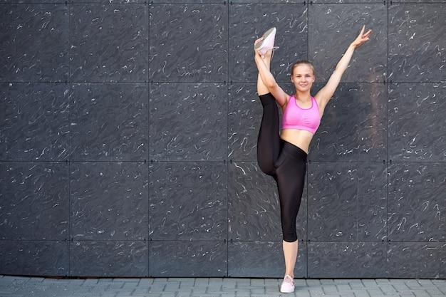 Vrouw uitrekken. fitness of gymnast of danser die oefeningen doet op grijze muurstad stedelijk