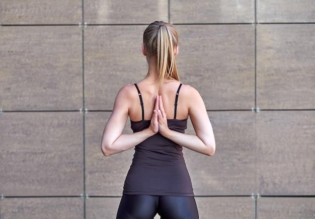 Vrouw uitrekken. fitness of gymnast of danser die oefeningen op bruine stedelijke muurmuur doen