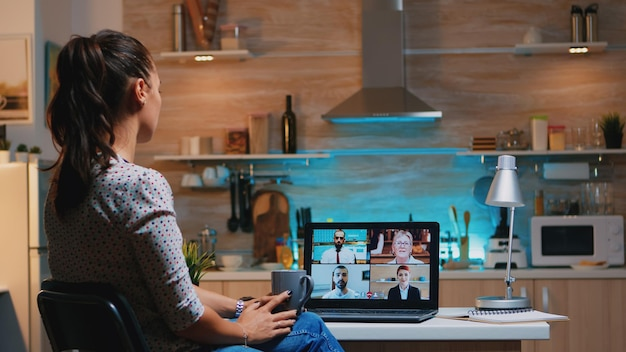 Vrouw valt in slaap tijdens videoconferentie op laptop die 's avonds laat thuis werkt in de keuken. met behulp van moderne technologie netwerk draadloos praten op virtuele vergadering om middernacht overuren maken