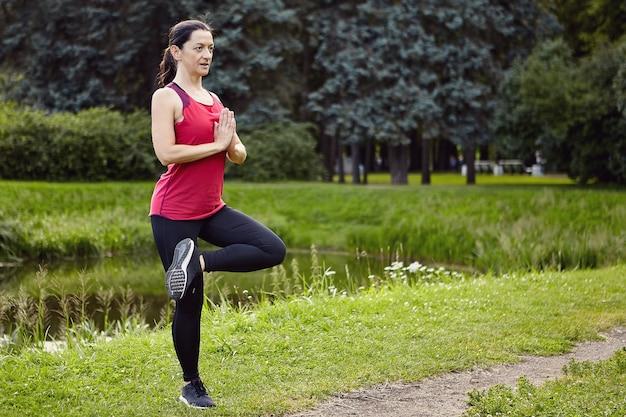 Vrouw van 40 jaar maakt fysieke oefeningen in de open lucht in sportkleding.