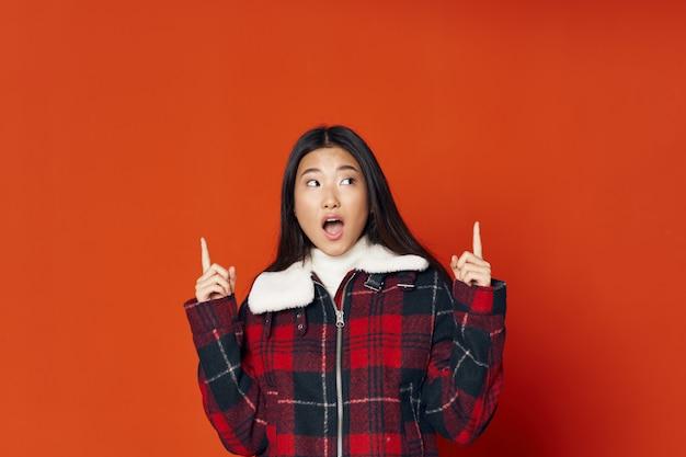 Vrouw van aziatische uitstraling in een geruite jas met handen gebaren