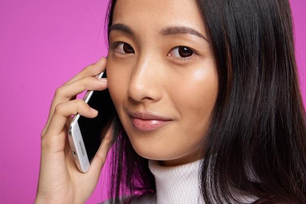 Vrouw van aziatische verschijning met een telefoon in hand mededeling close-uproze