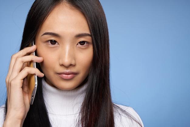 Vrouw van aziatische verschijning praten over het internet van de telefoontechnologie