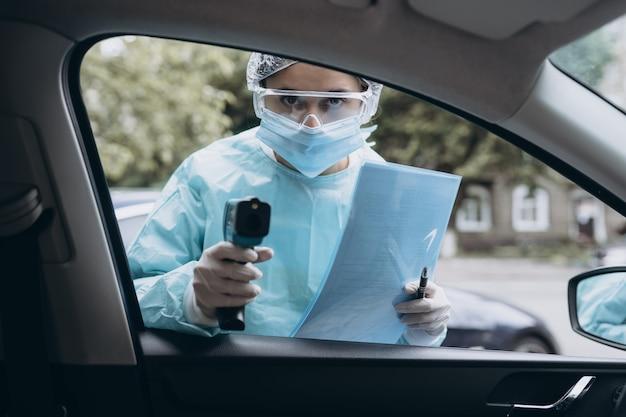 Vrouw van de arts gebruikt infrarood thermometer pistool om lichaamstemperatuur te controleren