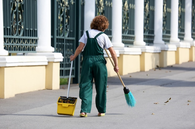 Vrouw van de conciërge reinigt de stoep van de stad van gevallen bladeren