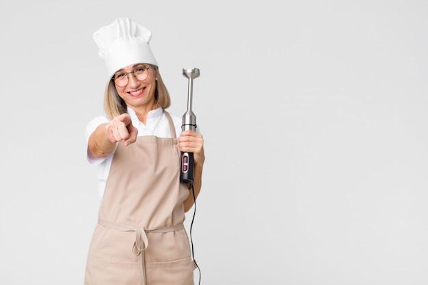 Vrouw van de middelbare leeftijd de mooie bakker met een mixer tegen exemplaar ruimtemuur