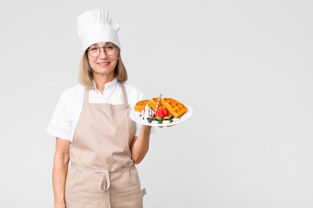 Vrouw van de middelbare leeftijd de mooie bakker met wafels tegen exemplaar ruimtemuur