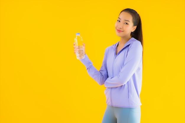 Vrouw van de portret de mooie jonge aziatische sport klaar voor oefening op geel