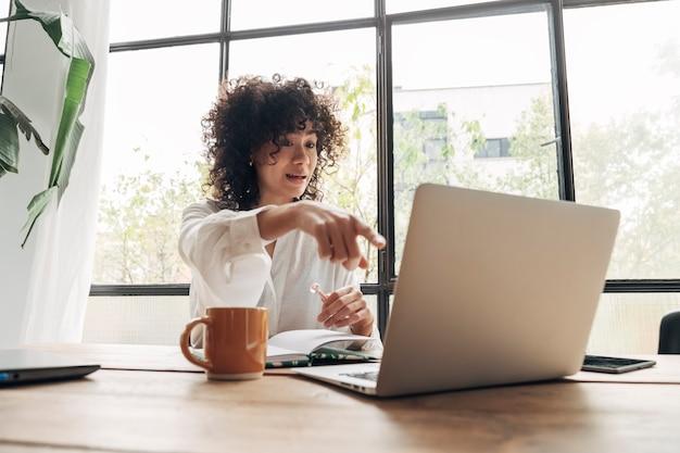 Vrouw van gemengd ras communiceert met collega op online werkvergadering videogesprek thuiswerken