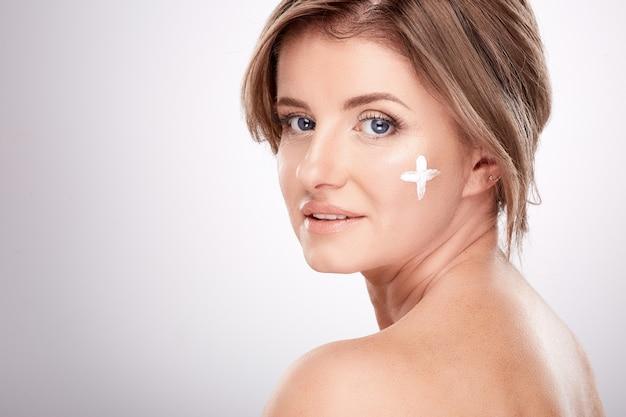 Vrouw van gemiddelde leeftijd met naakte make-up en blote schouders, concept van schoonheidsfoto, behandeling van huid en rimpels, uv-bescherming, gebruik van gezichtscrème, plus op de wang.