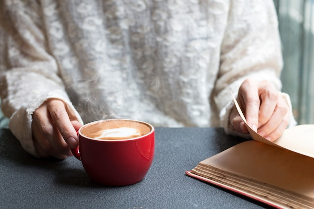Vrouw van handen die hete kop van koffie houden latte dichtbij het licht van de vensterochtend.