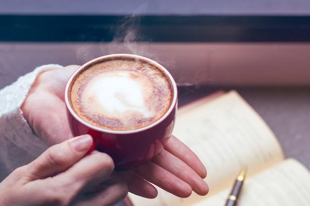 Vrouw van handen met warme kop koffie latte in de buurt van venster