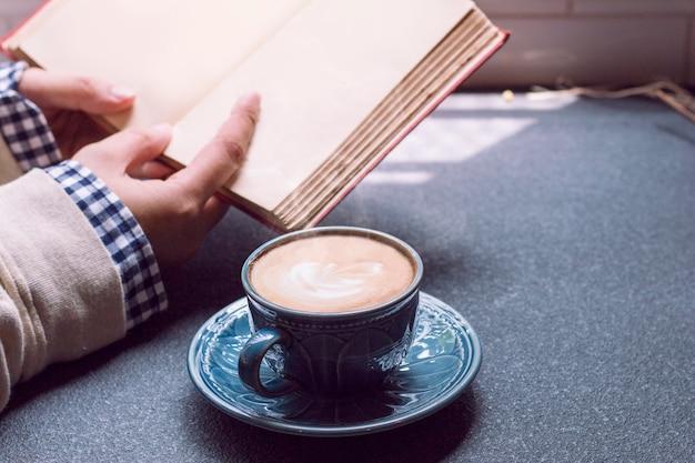 Vrouw van handen met warme kop koffie latte