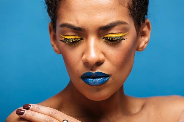Vrouw van het close-up de modieuze gespannen gemengd ras met trendy make-up die frustratie uitdrukken en neer kijken, geïsoleerd over blauwe muur