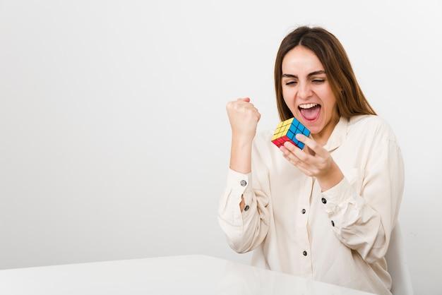 Vrouw van het vooraanzicht lost kubus rubiks op