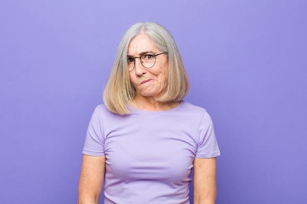 Vrouw van hogere of middelbare leeftijd die zich verward en twijfelachtig voelt, zich afvraagt of probeert te kiezen of een beslissing te nemen