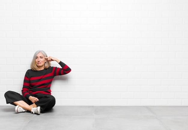 Vrouw van hogere of middelbare leeftijd die zich verward en verbaasd voelt, laat zien dat je gek, gek of gek bent