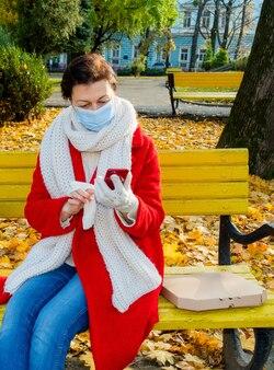 Vrouw van middelbare leeftijd 50 plus met beschermend medisch masker zittend op een gele bank in herfst park met telefoon en doos voor pizza. levering of afhaalconcept.