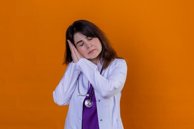 Vrouw van middelbare leeftijd arts dragen witte jas en met stethoscoop op zoek overwerkt poseren met handen samen terwijl staande met gesloten ogen wil slapen op oranje achtergrond