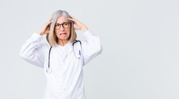 Vrouw van middelbare leeftijd, arts, gefrustreerd en geïrriteerd, ziek en moe van mislukking, beu met saaie, saaie taken