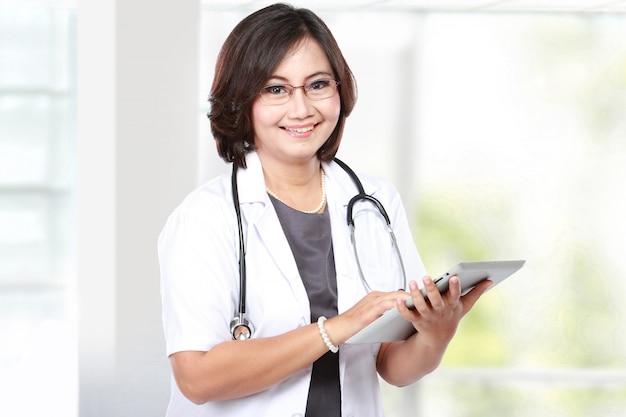 Vrouw van middelbare leeftijd arts met behulp van tablet-computer