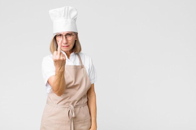 Vrouw van middelbare leeftijd, bakker, boos, geïrriteerd, rebels en agressief, de middelvinger omdraaiend en vechtend tegen de platte muur